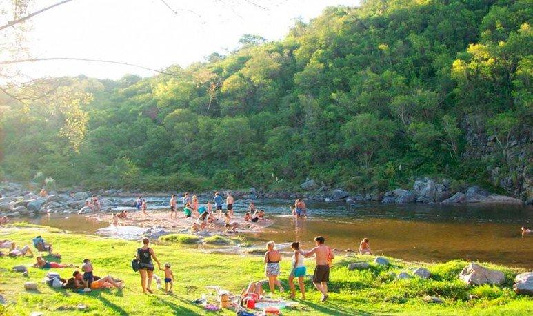 Gente a orillas del río en La Serranita Córdoba
