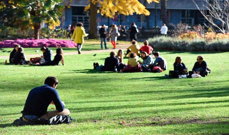 Jóvenes sentados en el cesped en Plaza